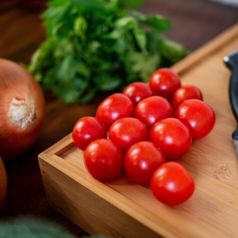 Tomatoes, onion and basil on a wood cutting board