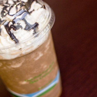 Cold coffee beverage with whipped cream and chocolate drizzle