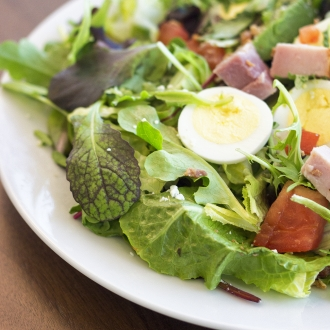 Salad on a plate with mixed greens, eggs and ham