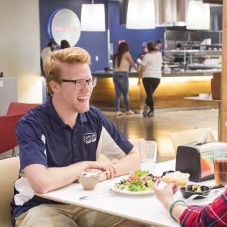 Two students sitting and dining at The Kitchens dining venue