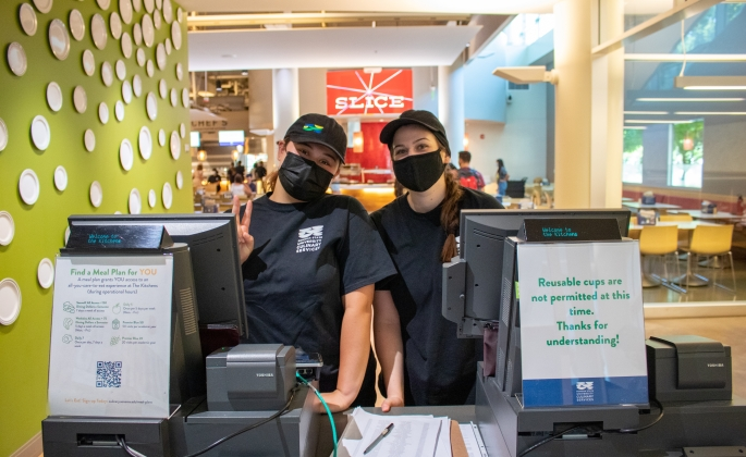 Two culinary employees standing behind registers