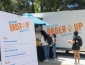 People standing in line to pick up food with a white food truck behind them